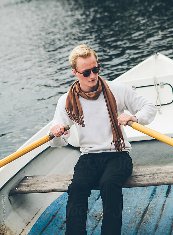 Elegant young man rowing in a lake by kkgas for Stocksy United