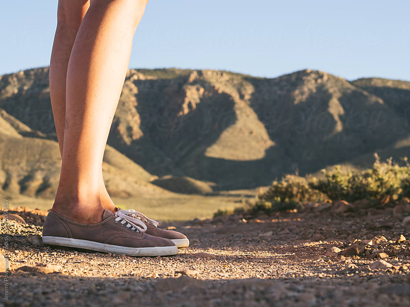 Close up of young woman in shoes on hiking trail leading to mountains by Jeremy Pawlowski for Stocksy United