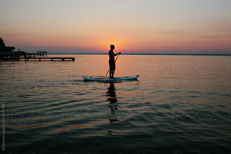 silhouette of a man on a paddle board at sunset by Kelly Knox for Stocksy United