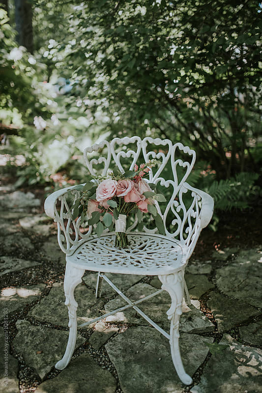 Bouquet on White Iron Chair by Kim Swain for Stocksy United
