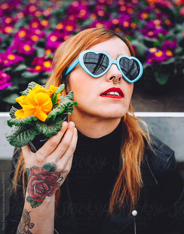 girl with flower in hand wears a   glasses heart by Thais Ramos Varela for Stocksy United
