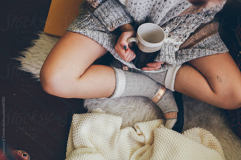 Woman sitting in a cozy sweater drinking coffee by Treasures & Travels for Stocksy United