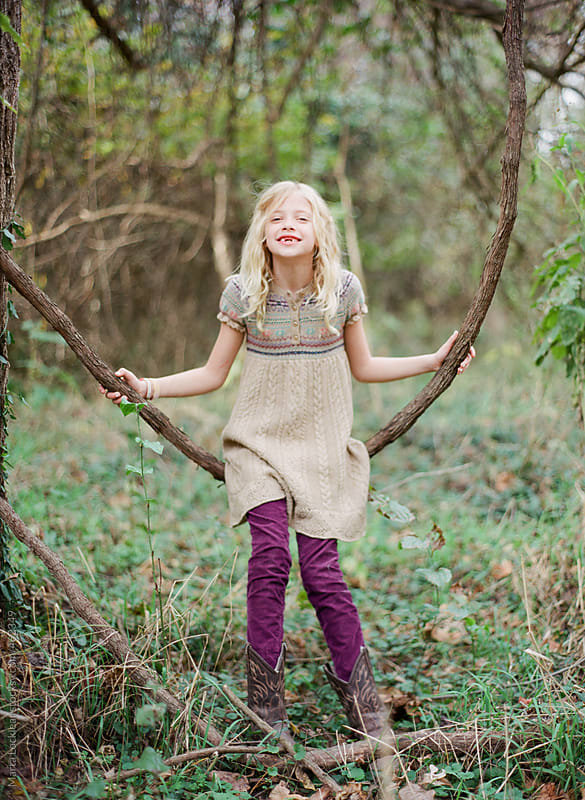Young girl sitting and swinging on a vine swing in the woods by Marta Locklear for Stocksy United
