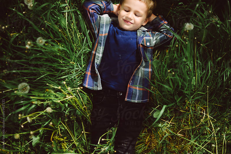 boy lying in the grass by Jovana Vukotic for Stocksy United