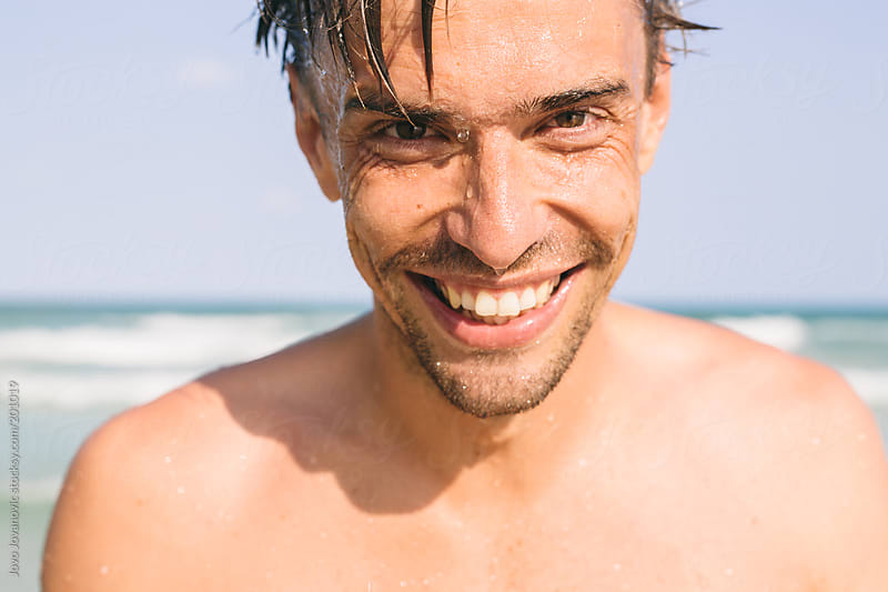 Portrait of a smiling man who just came out from the water by Jovo Jovanovic for Stocksy United