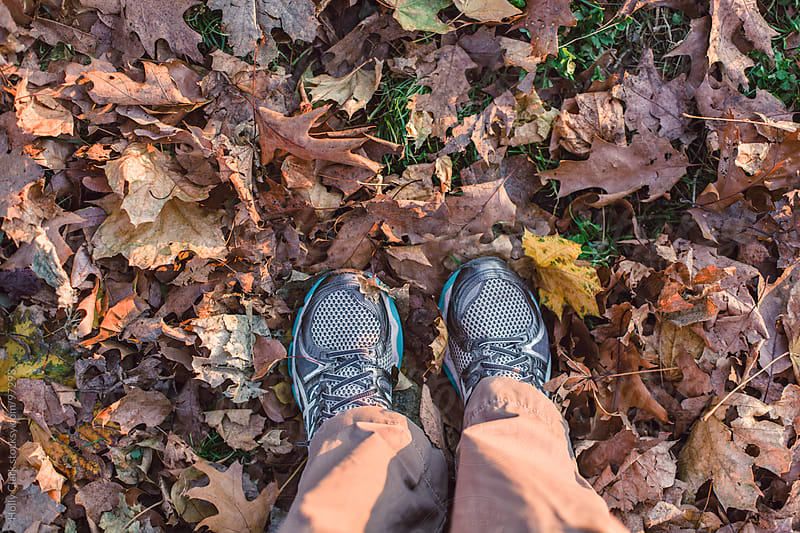 Feet standing in a pile of autumn leaves. by Holly Clark for Stocksy United