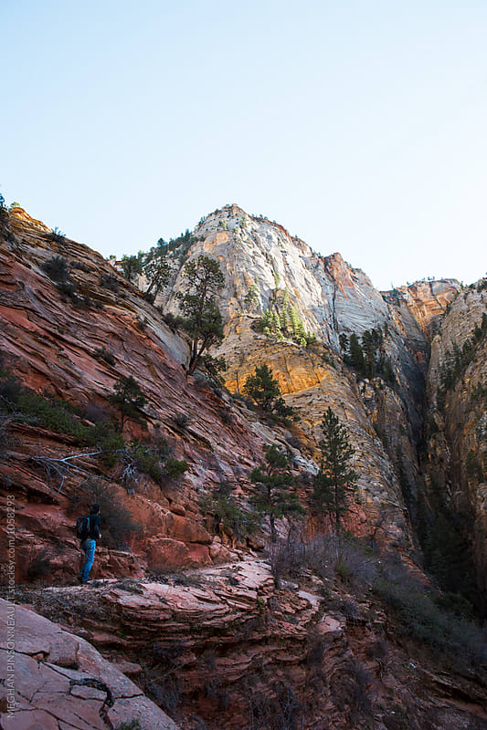 Hiker on Trail with Colorful Canyon Walls by MEGHAN PINSONNEAULT for Stocksy United