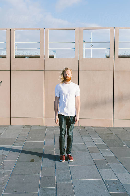 Tough young man with a red beard standing tall in the strong wind by Denni Van Huis for Stocksy United