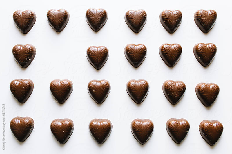 Grid of chocolate hearts with one missing by Carey Shaw for Stocksy United