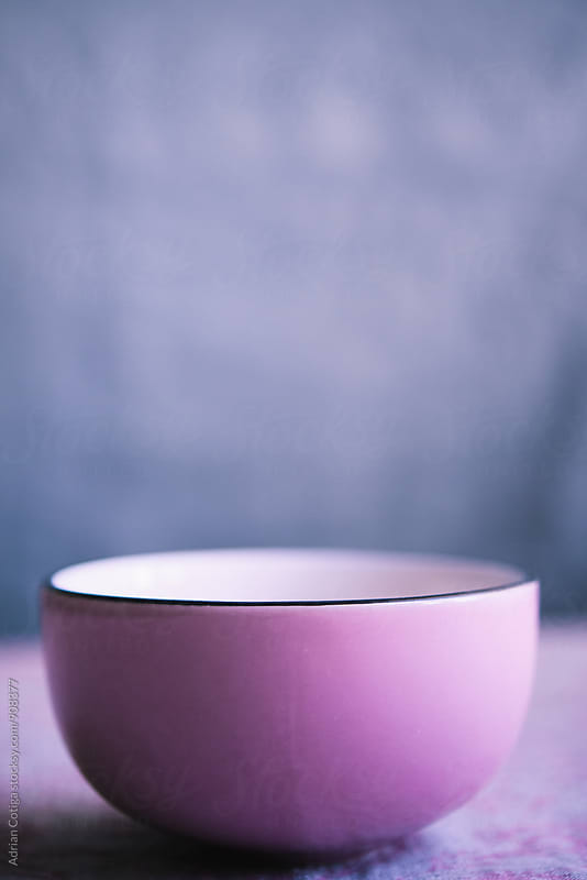 Pink bowl over a blue background by Adrian Cotiga for Stocksy United
