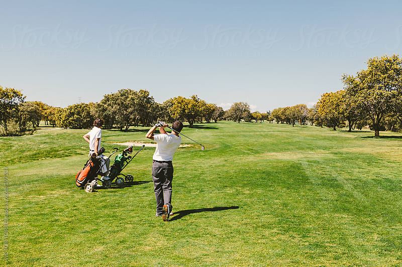 Two Men Playing in a Golf Course by VICTOR TORRES for Stocksy United