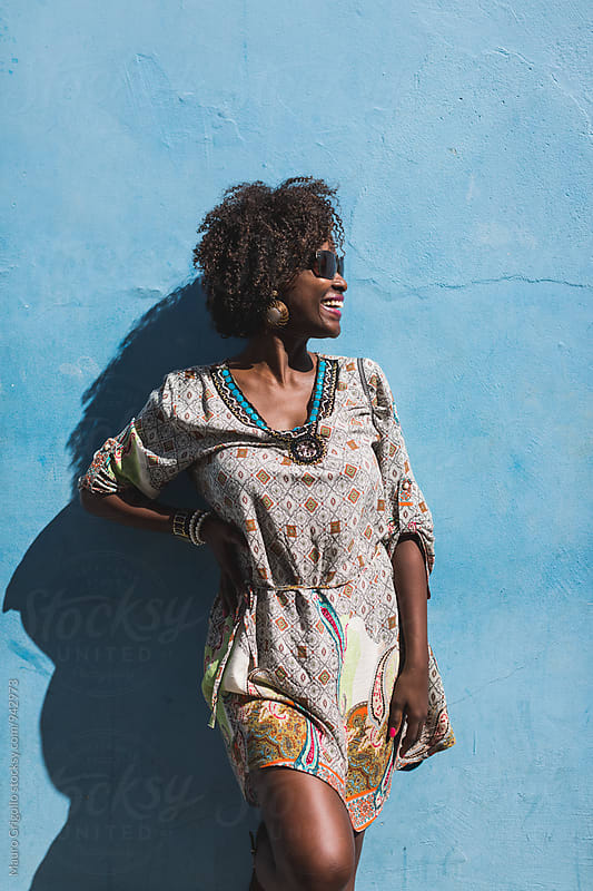Brazilian Woman on blue wall. Copy space. by Mauro Grigollo for Stocksy United