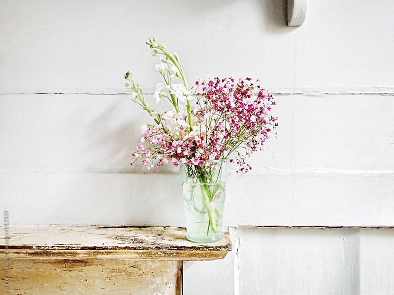 Wild flowers in a glass vase on a shelf by James Ross for Stocksy United
