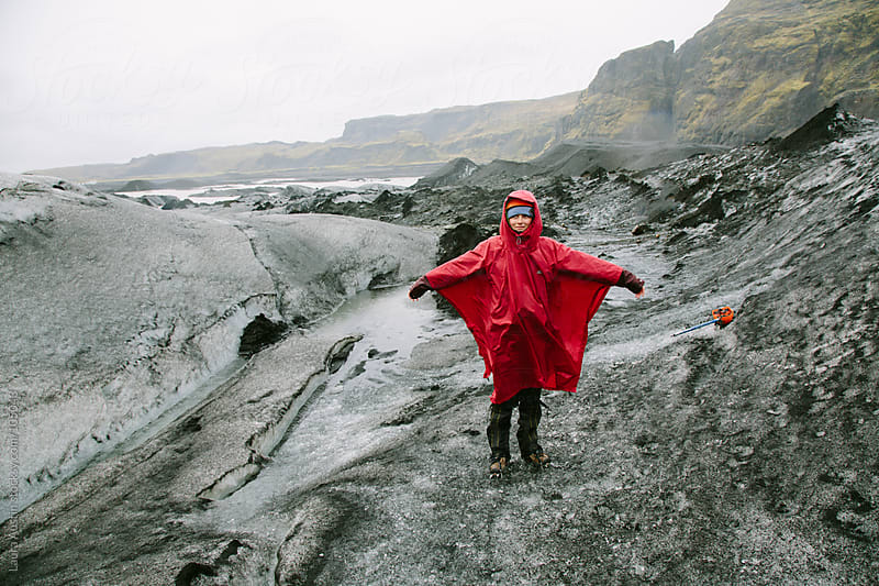 Young Woman Standing In The Middle Of A Glacier by Laura Austin for Stocksy United