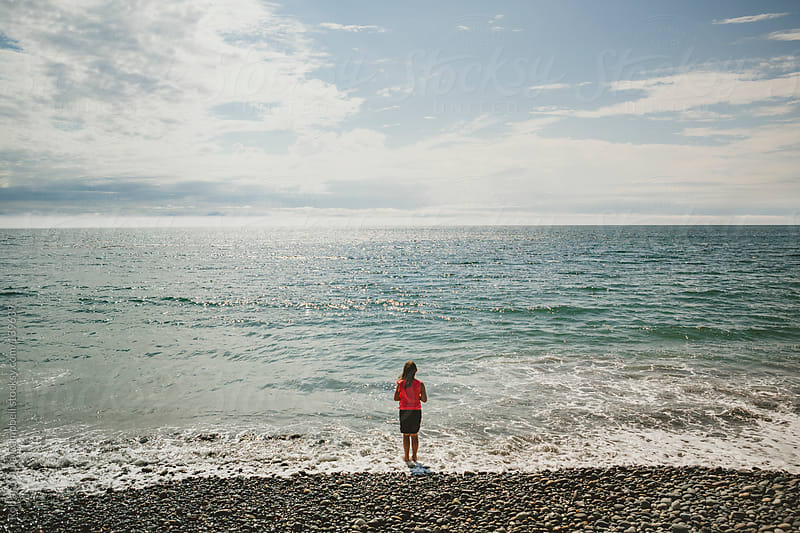 Young girls standing on beach looking out to sea by Rob and Julia Campbell for Stocksy United