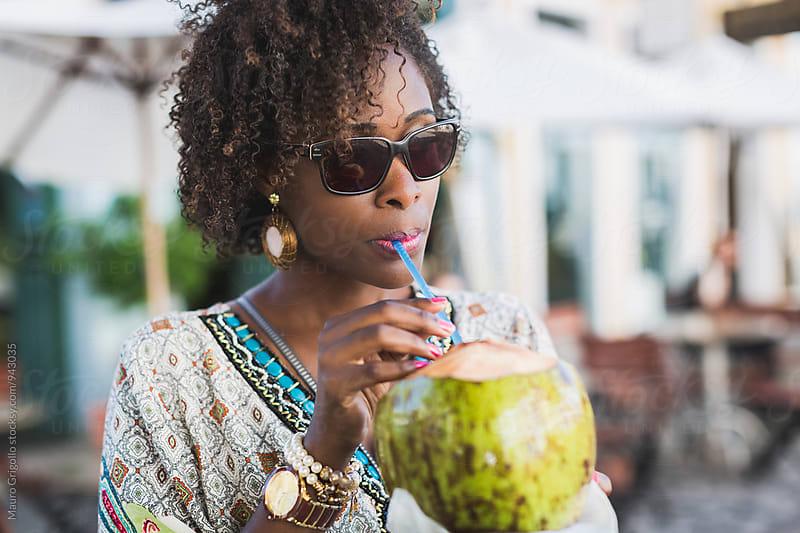 Brazilian Woman drinking coconut water by Mauro Grigollo for Stocksy United