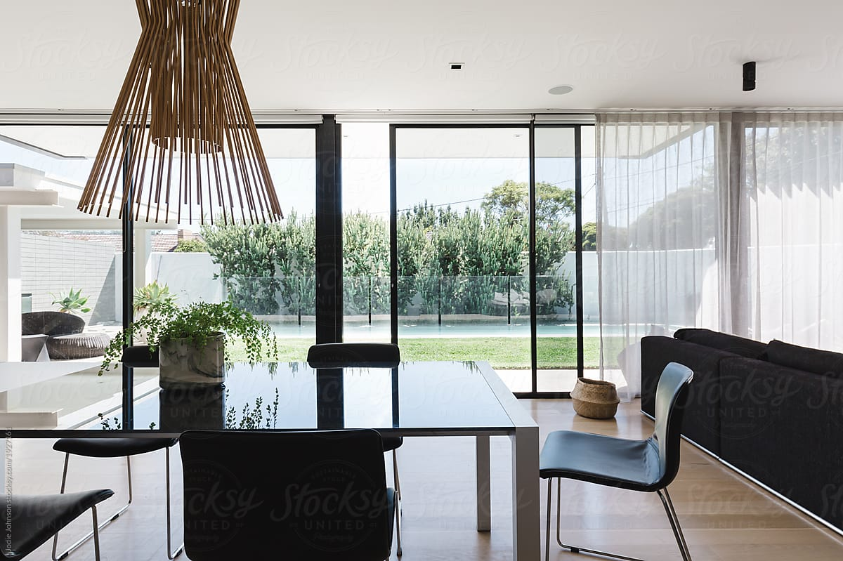 Dining Room Table With Large Glass Sliding Doors Looking Out On To The Backyard And Pool
