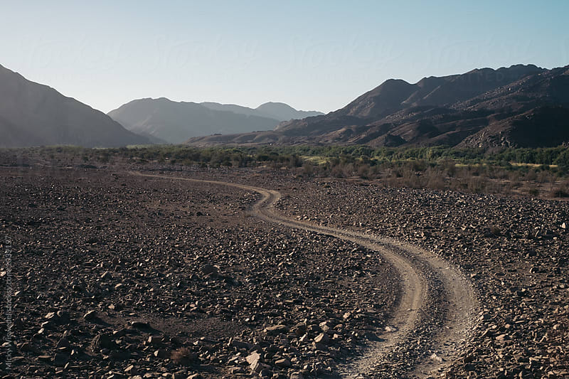 Winding dirt track in a rocky desert landscape by Micky Wiswedel for Stocksy United