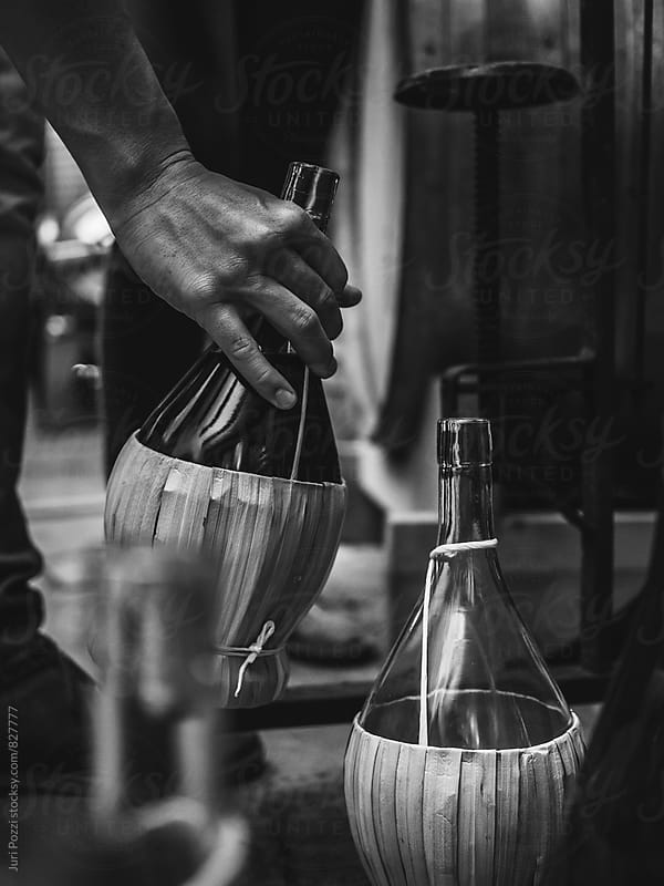 Young man closing wine bottles by Juri Pozzi for Stocksy United