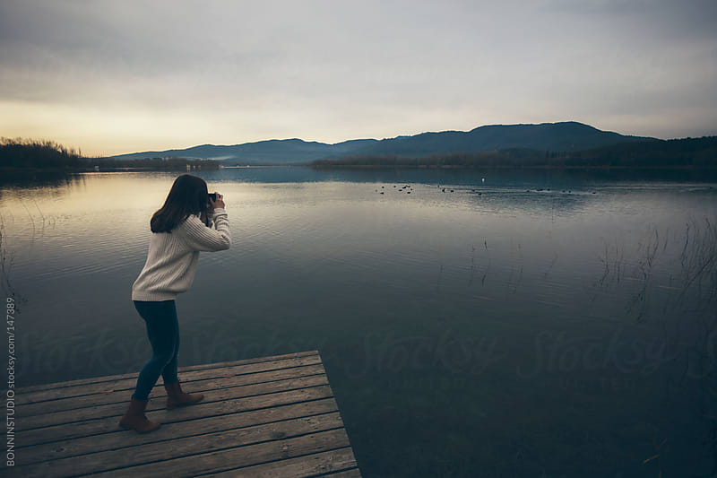 Young woman taking a photo with old camera at the lakeshore. by BONNINSTUDIO for Stocksy United