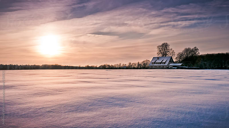 Colorful Sunrise on Snow Covered Field with Farmhouse by Andreas Wonisch for Stocksy United