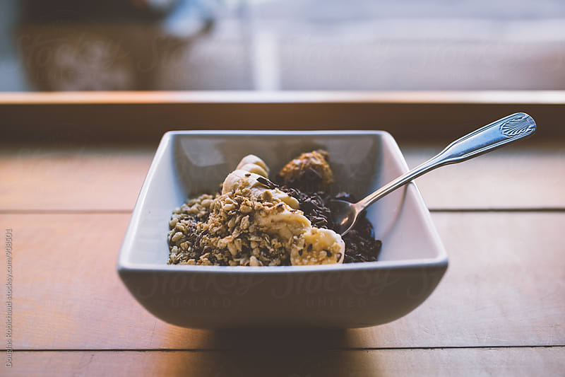 Delicious acai bowl with bananas and peanut butter by Douglas Robichaud for Stocksy United