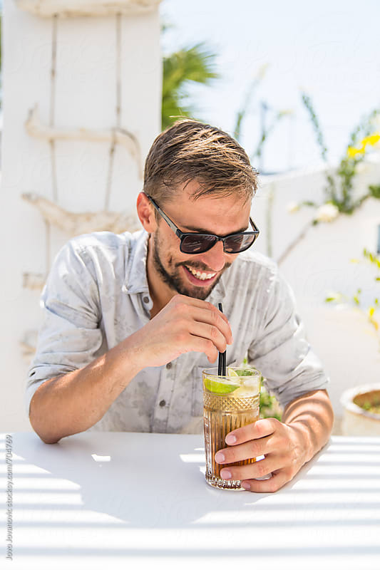 Young man drinking cocktail in a white bar by Jovo Jovanovic for Stocksy United