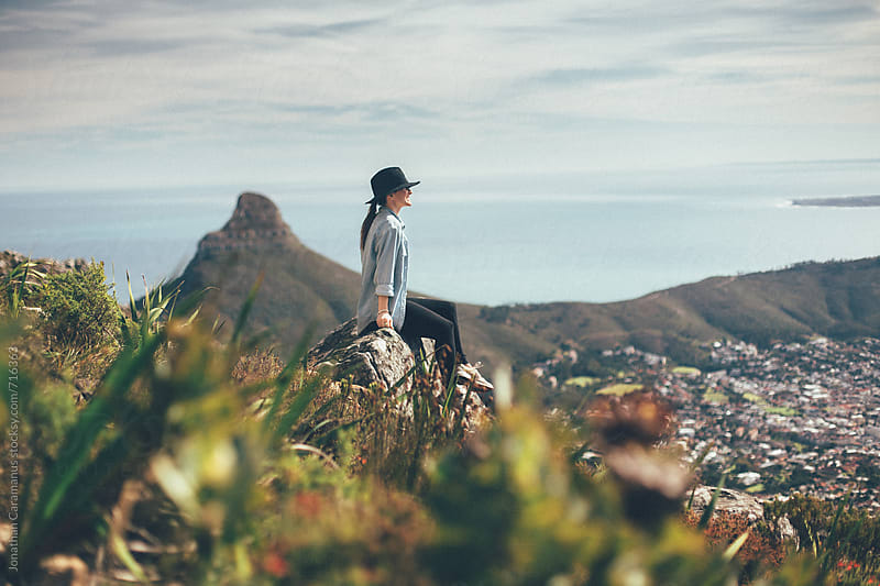 woman wearing hat sitting on mountain overlooking view by Jonathan Caramanus for Stocksy United