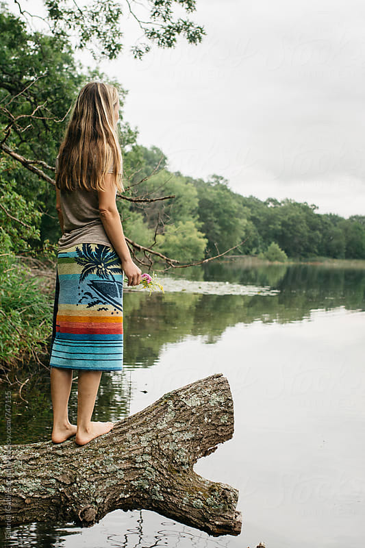 Woman with beach towel around her waist standing on a tree log by a lake by Gabriel (Gabi) Bucataru for Stocksy United