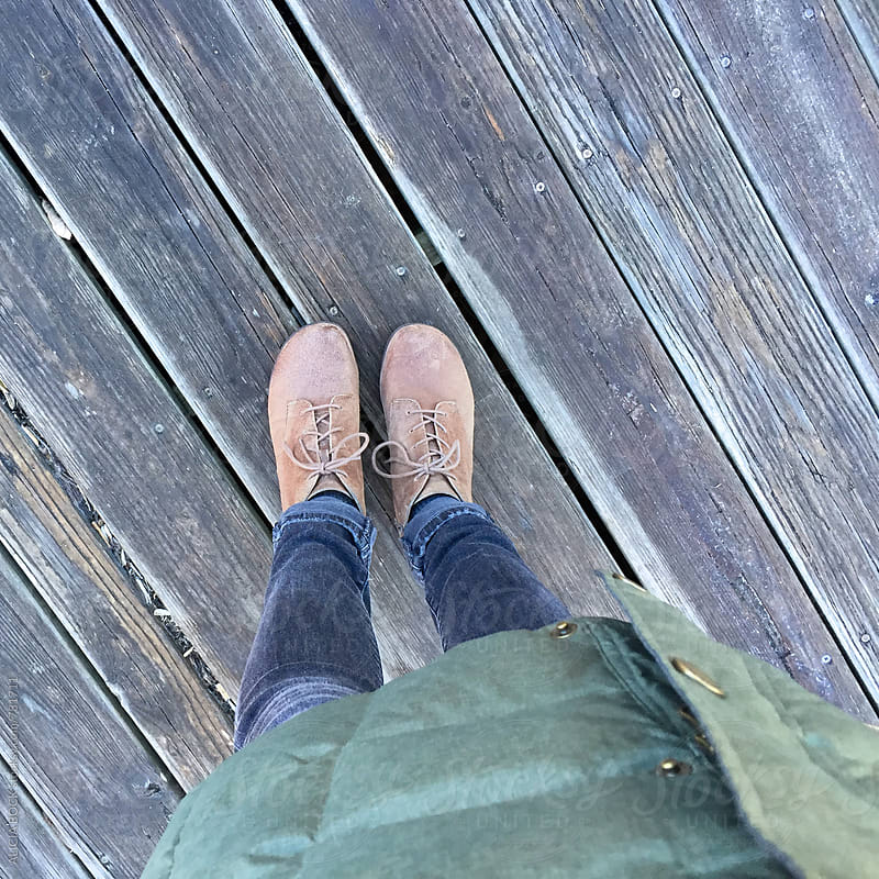 A Woman's Feet Standing On A Wood Deck On An Autumn Day by ALICIA BOCK for Stocksy United