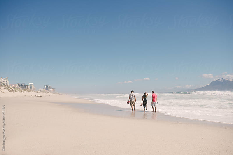 Friends taking a long walk on the beach by Aila Images for Stocksy United