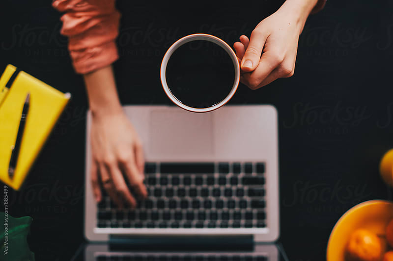 Woman drinking coffee and working on a laptop by VeaVea for Stocksy United