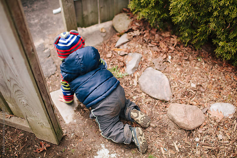 Little boy crawling out of a gate escaping with a vest and hat on. by Sarah Lalone for Stocksy United