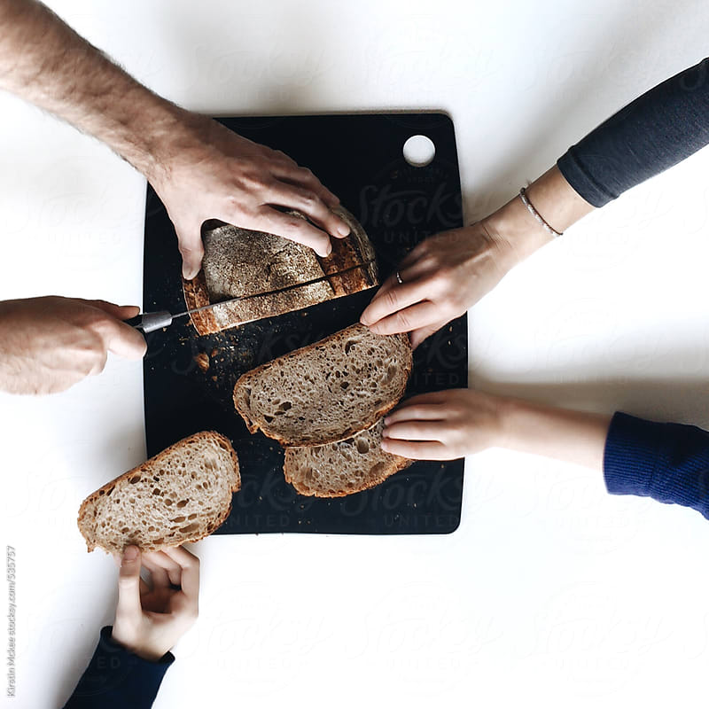 A family sharing a loaf of sourdough bread by Kirstin Mckee for Stocksy United