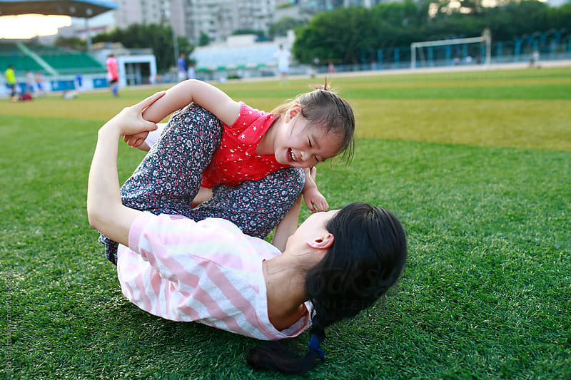 little girl having fun with her mother outdoor by cuiyan Liu for Stocksy United