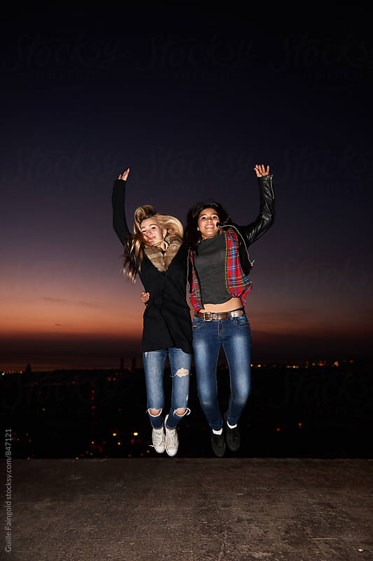 Two young women jumping against of evening cityscape by Guille Faingold for Stocksy United