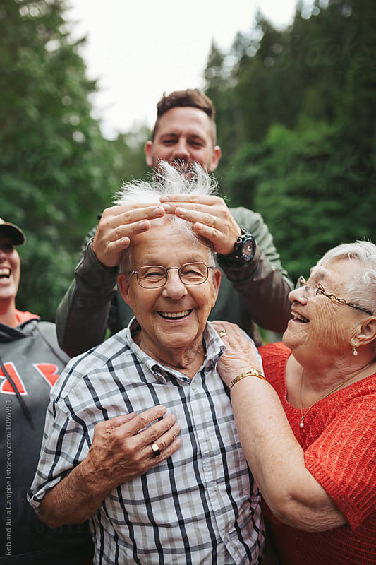 Joking grandkids mess up grandpa's hair by Rob and Julia Campbell for Stocksy United