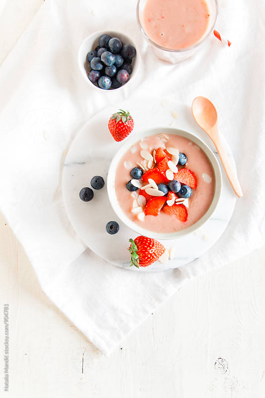 Strawberry smoothie bowl with blueberries and almonds by Nataša Mandić for Stocksy United