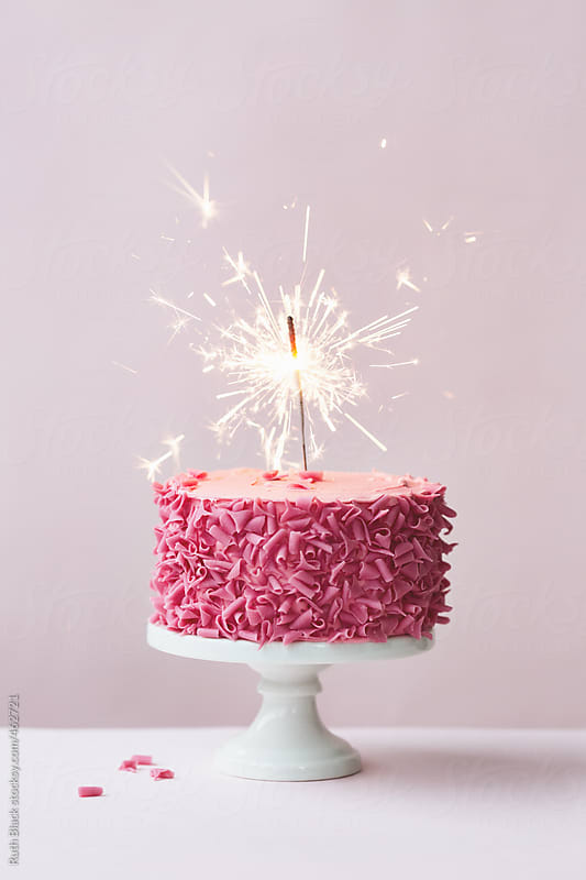Cake with pink chocolate curls and sparkler by Ruth Black for Stocksy United