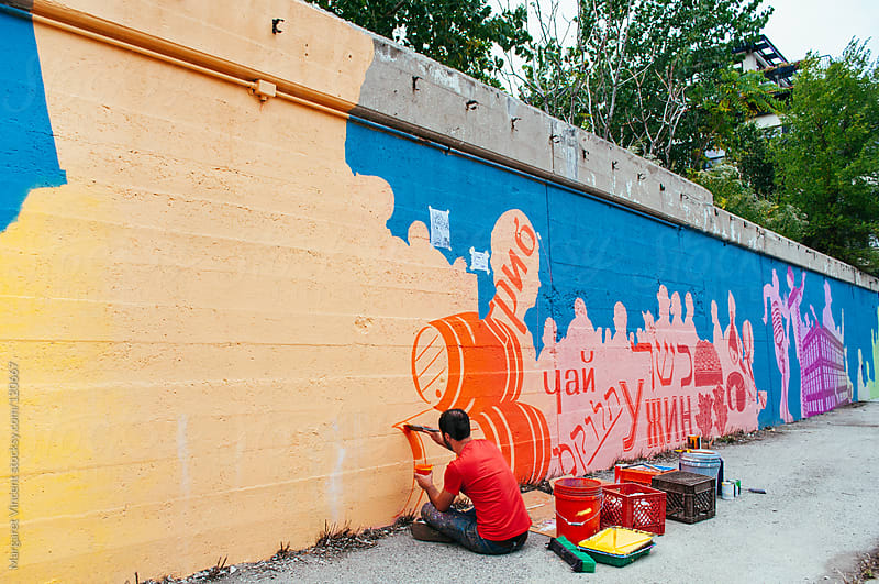 artist paints mural on a city street by Margaret Vincent for Stocksy United