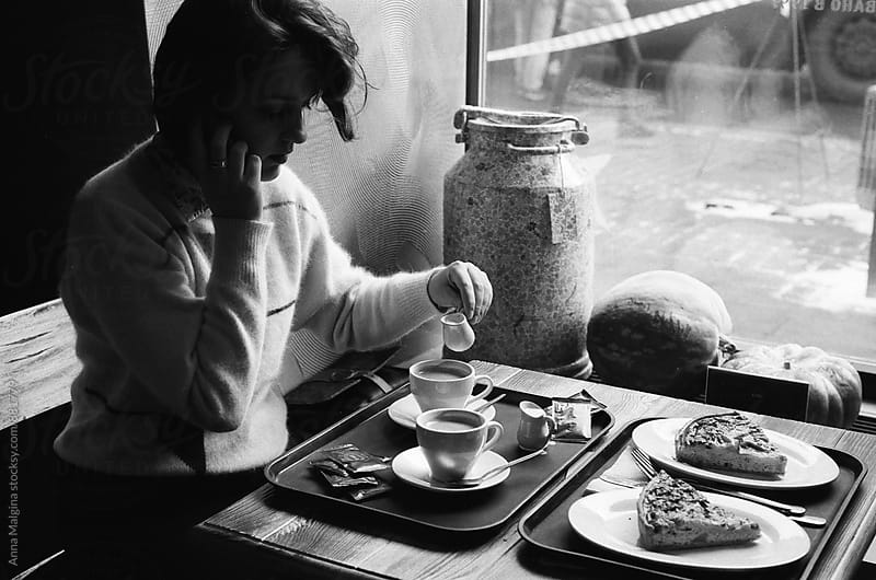 A black and white film photo of  young woman talking by telephone in the coffeehouse by Anna Malgina for Stocksy United