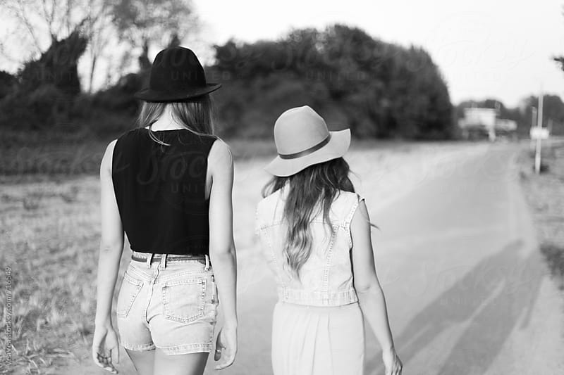 Two stylish young woman from the back walking down an empty road. Black and white by Marija Mandic for Stocksy United