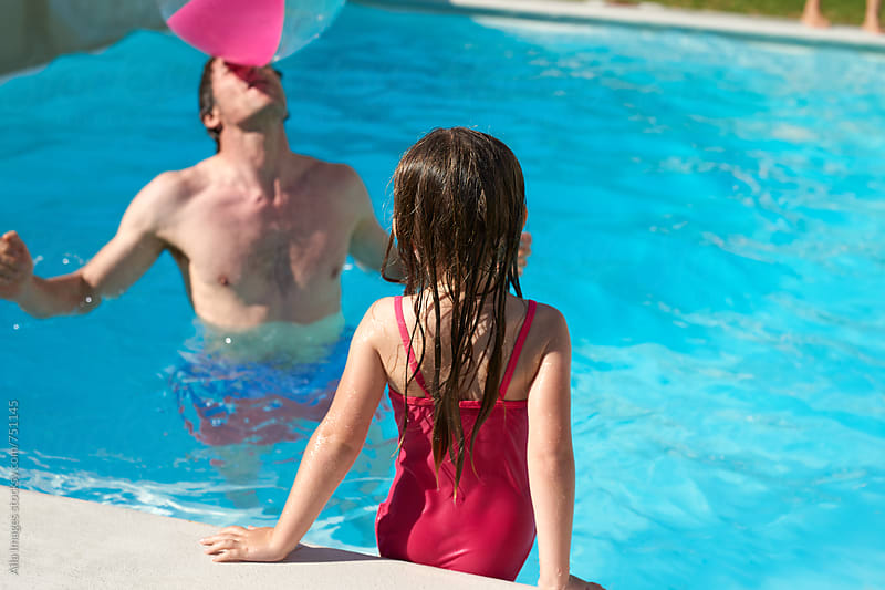 Dad balancing ball on his nose playing with daughter in pool by Aila Images for Stocksy United