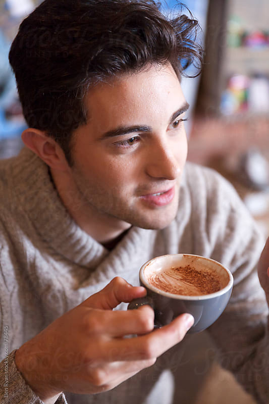Trendy male engaged in conversation in a trendy cafe by Ben Ryan for Stocksy United