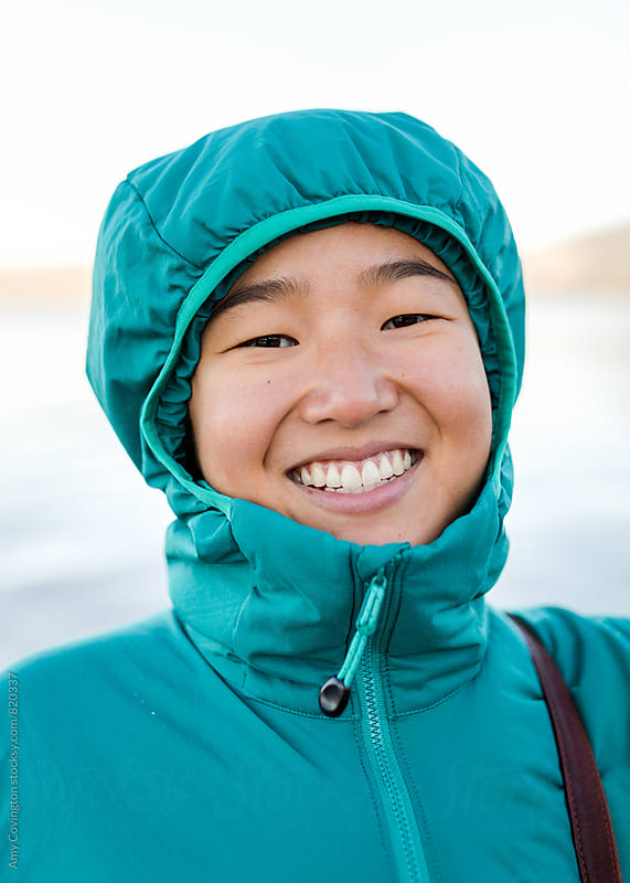 Beautiful young woman wearing a winter coat and smiling  by Amy Covington for Stocksy United