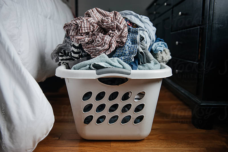 Basket of dirty laundry on the bedroom floor by Cara Dolan for Stocksy United