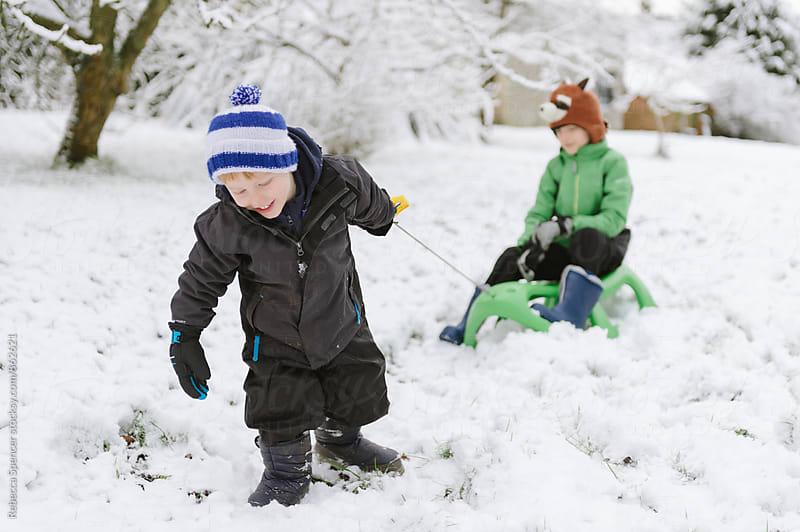 Brothers with toboggan play in the snow by Rebecca Spencer for Stocksy United