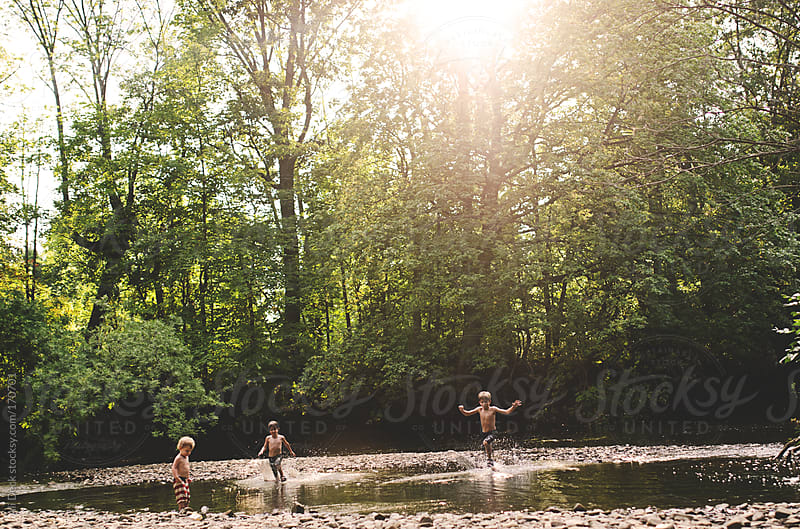 Three Boys in a Creek by Ali Deck for Stocksy United