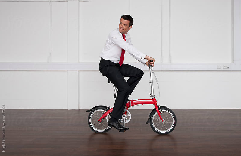 Businessman using bicycle at work by Hugh Sitton for Stocksy United