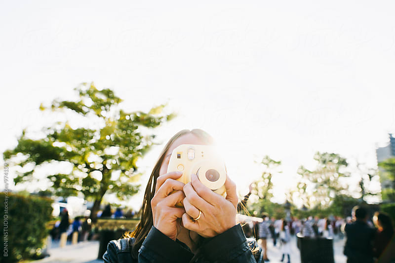 Tourist woman taking a photo with her instant camera.  by BONNINSTUDIO for Stocksy United